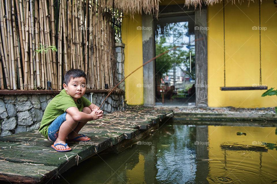 Asian boy fishing in pool