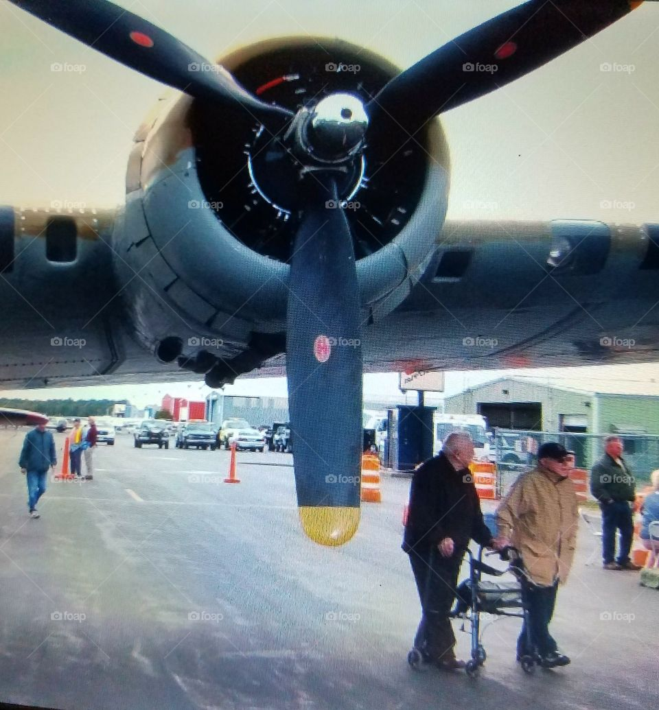 WWII vintage Bomber wing with enormous propellers. The two older men are U.S. Veterans🇺🇸, one uses a Walker & the other needs to use an Oxygen tank to breathe.