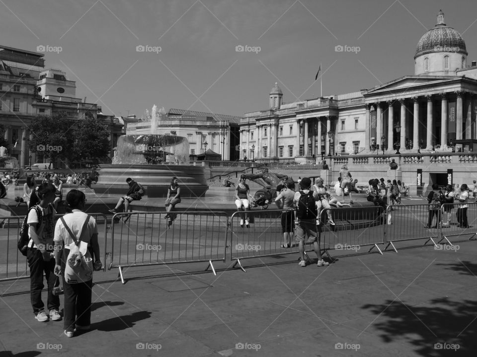 Crowds of people walk in an open square with a beautiful fountain in London on a sunny summer day.