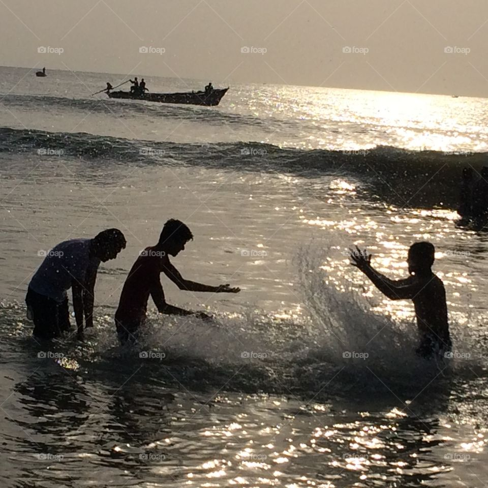 playing guys in beach water, beautiful scenery