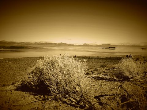 Oasis. Desert lake surrounded by mountains, scenery with antique finish.