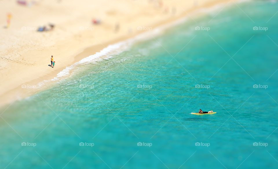 A view from above looking down onto a white sandy beach and emerald green ocean with small people and surf boarders enjoying the sunshine and summer vacation.