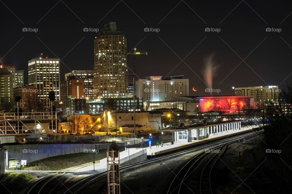 Foap, Day and Night: Nighttime skyline of Raleigh North Carolina as seen from Boylan Bridge. Scene includes the train station, the color-changing shimmer wall (currently red), and the orange crescent moon tucked away in a corner among the buildings.