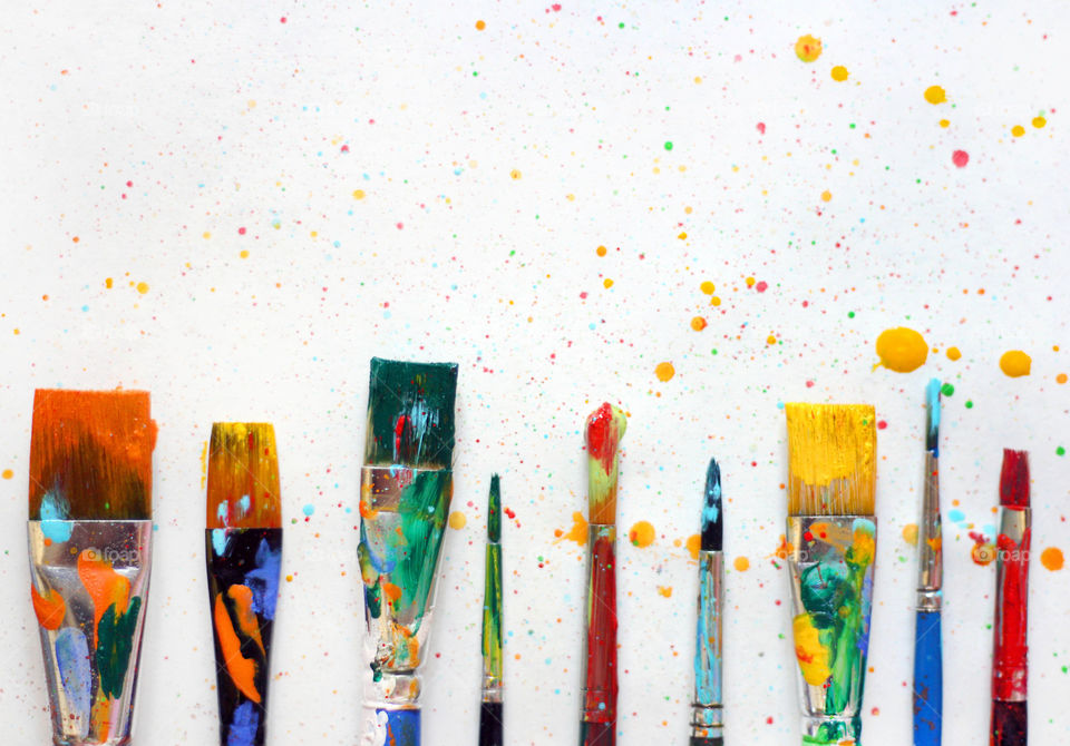 Colorful painted paintbrushes in a row, colorful dots of paint on the white background