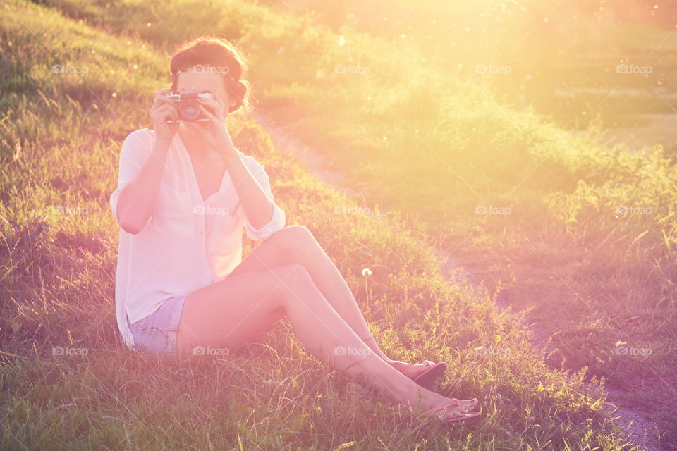 Woman photographing on grassy field