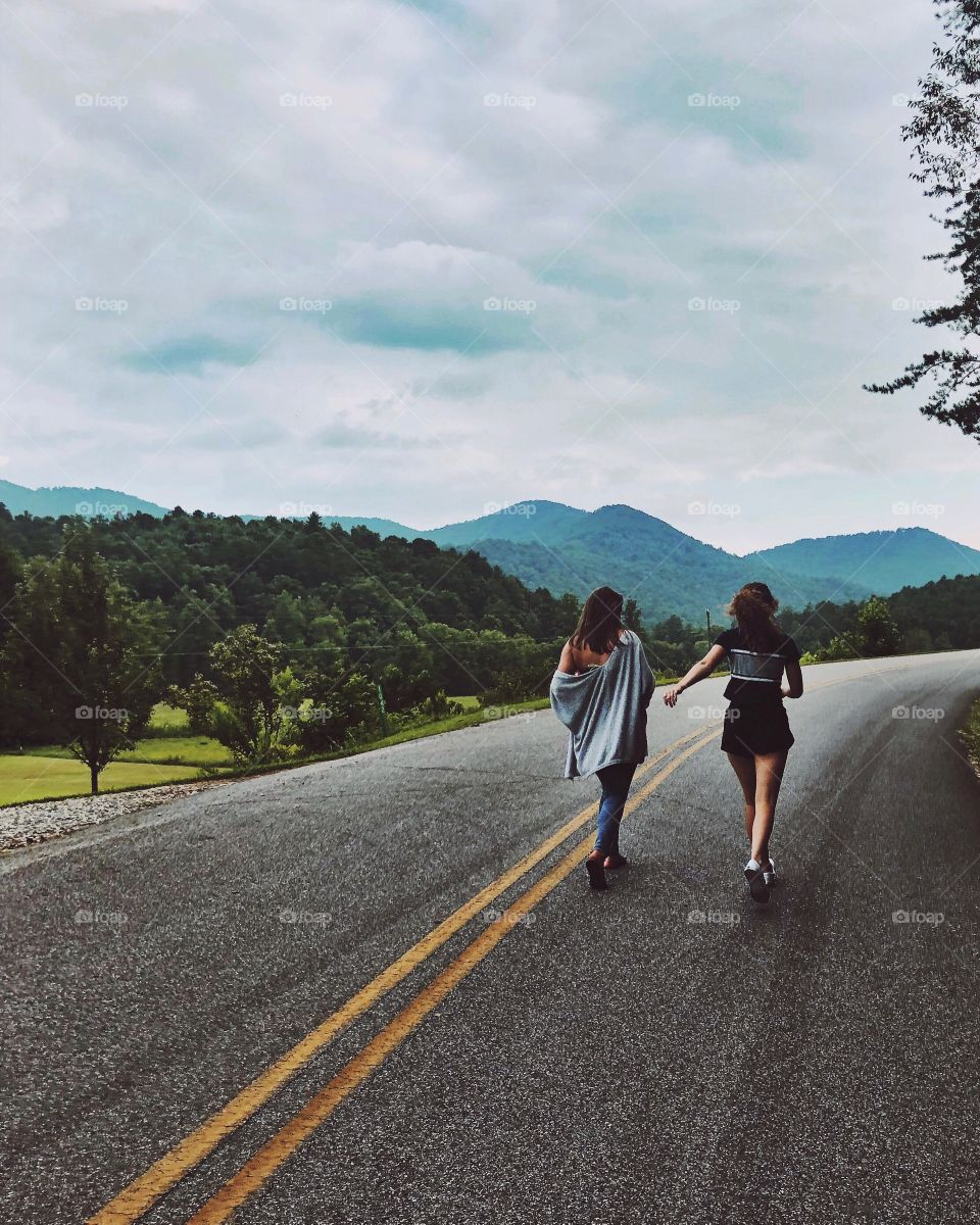 Two girls walking on a long road to nowhere