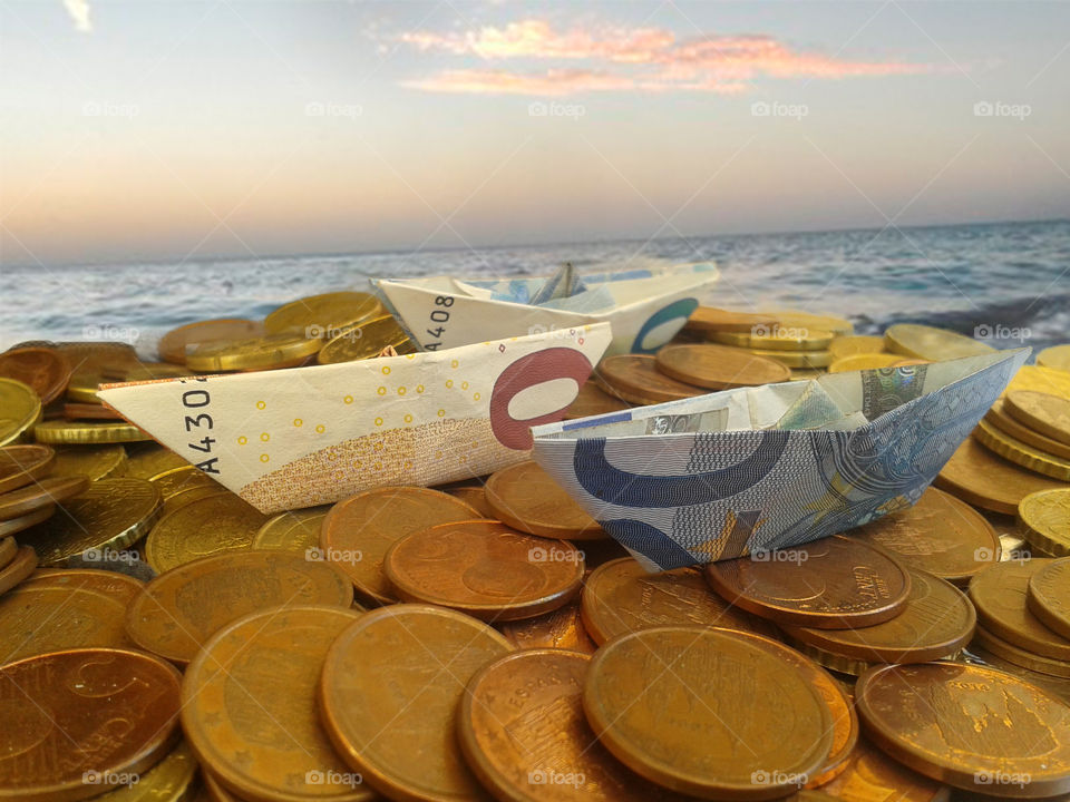 Coins and euro note on beach