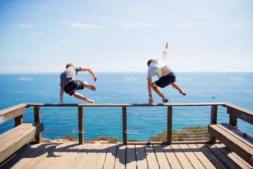 Two people jumping off boardwalk