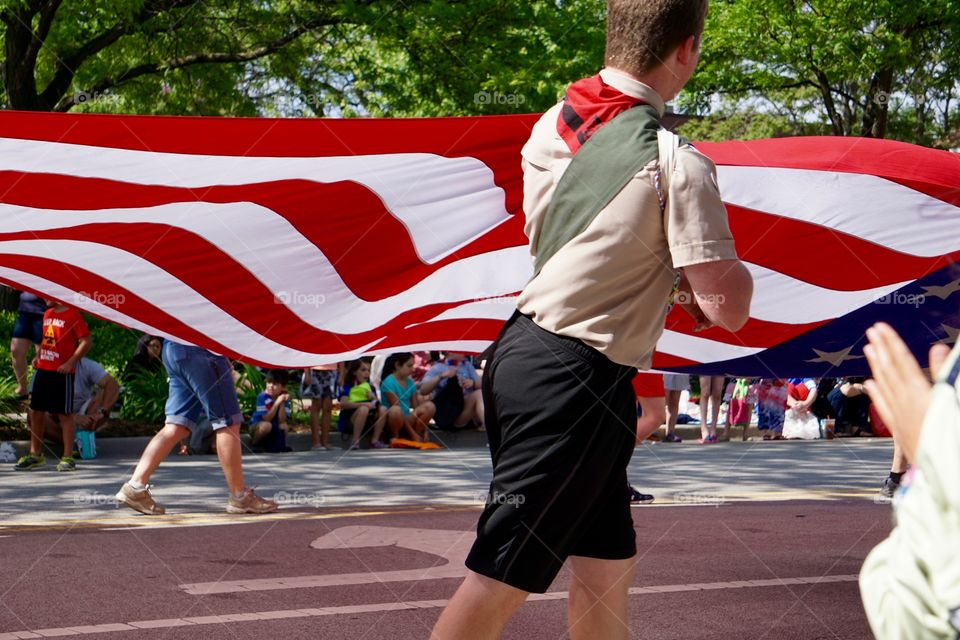 Boy Scout pulls on large American flag in parade