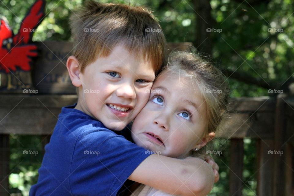 Boy hugging her sister