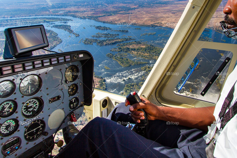 One of the most amazing hobbies -flying!  Image of helicopter pilot, inside of helicopter and scenic view over a river in Africa
