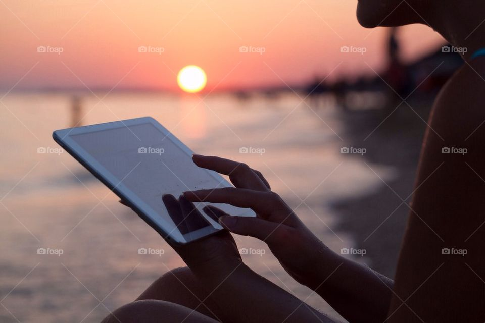 Woman by the sea and working on a tablet