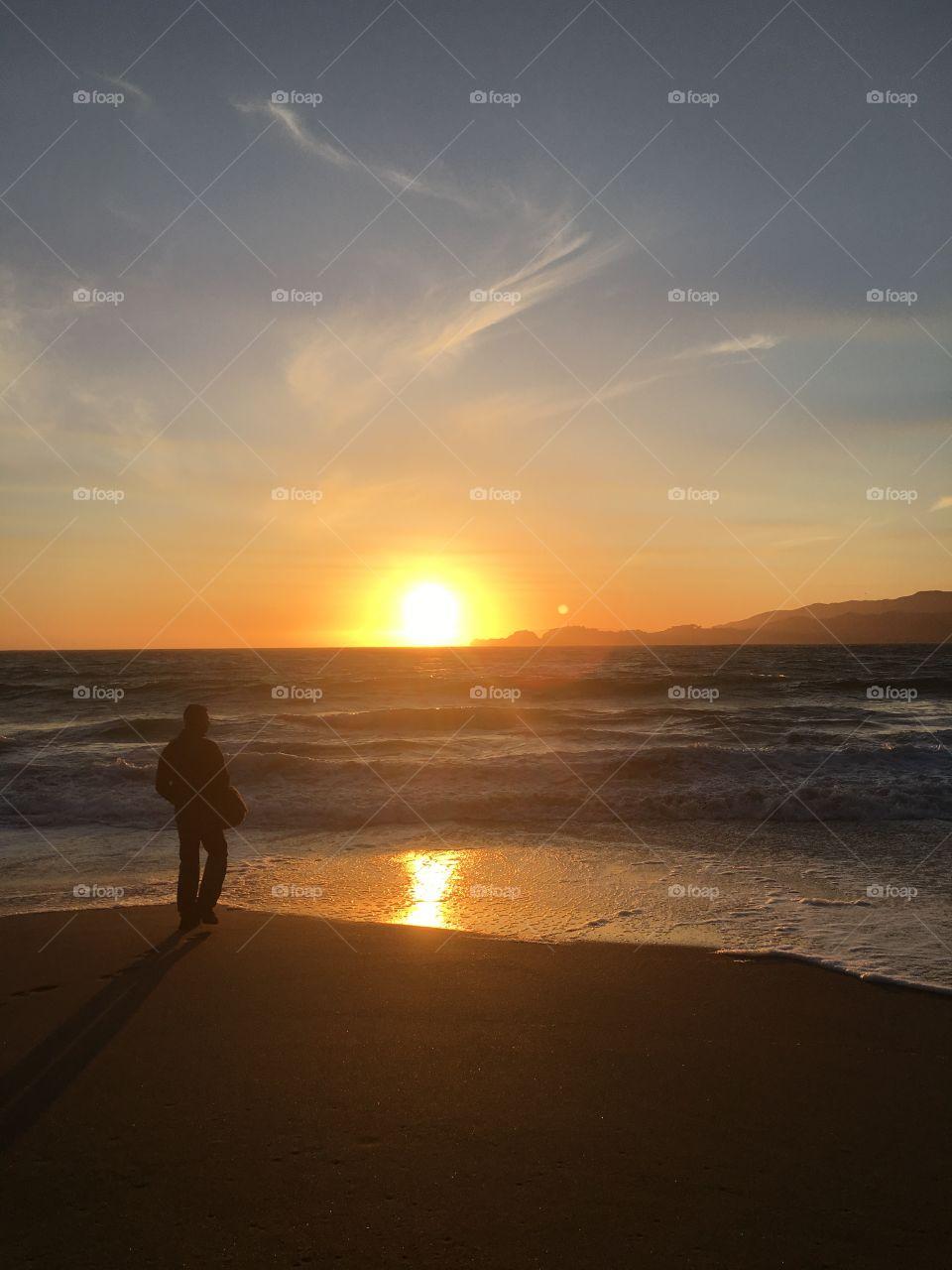 Man looking at sunrise at sea