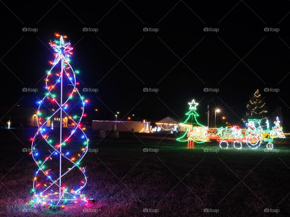 A beautiful outdoor Christmas light display shaped like a tree and a train driven by Santa lit up at night.