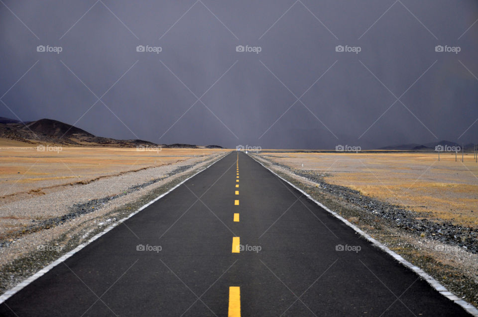 Empty road leading toward mountains