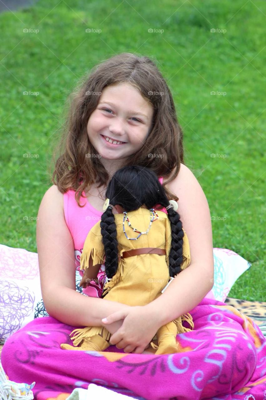 My American Girl. Pretty young lady playing with her American Girl doll.