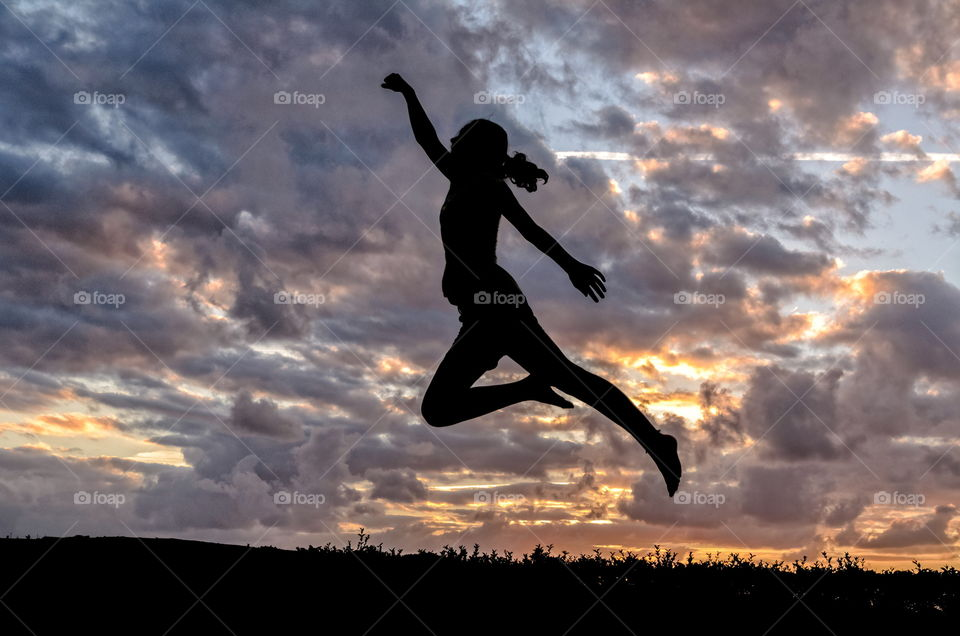 Silhouette of a girl jumping as a super heroe at sunset