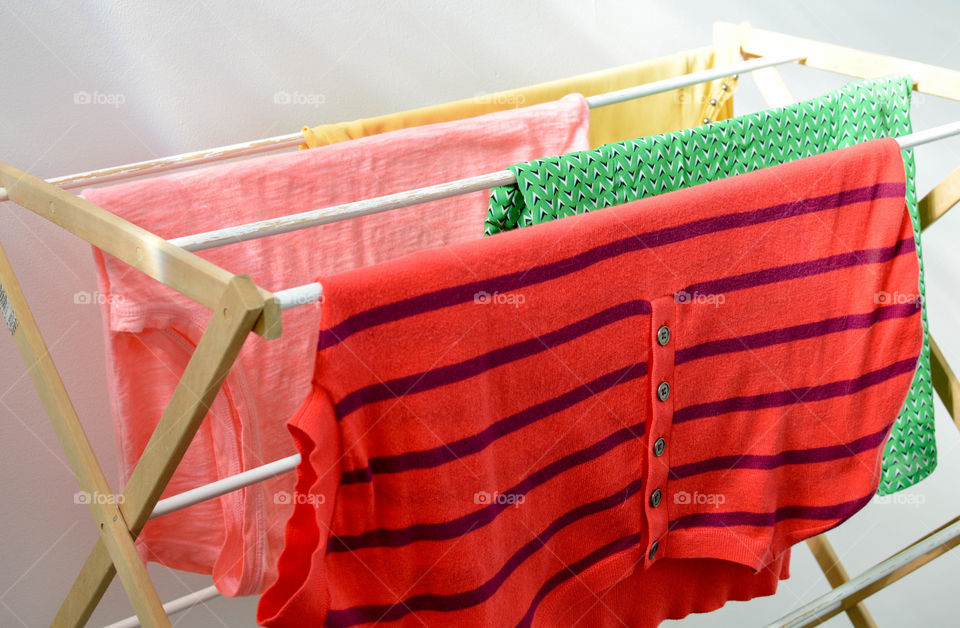 Colorful shirts hanging on a clothes rack to dry