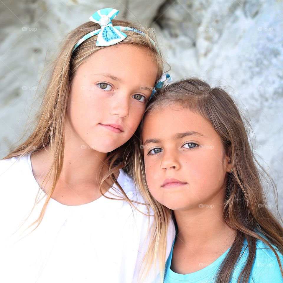 Outdoor beach portrait of two young sisters girls with serious pleasant expressions long hair headband bow with white and teal outfits