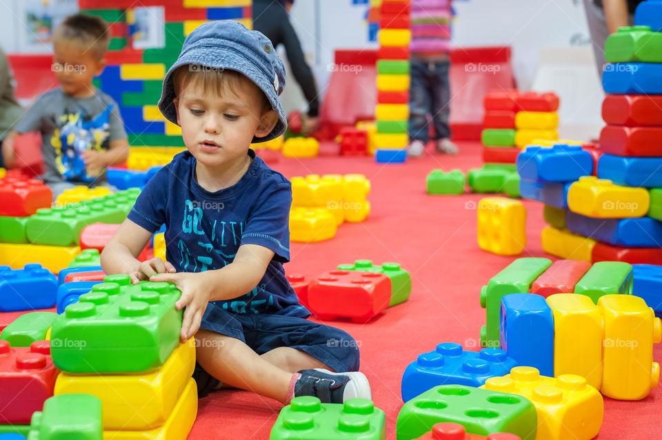 Little boy playing with big blocks.