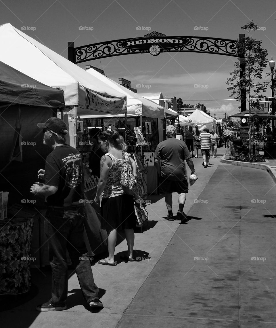 A crowd of people viewing sellers wares at a street fair in Redmond in Central Oregon on a sunny summer day.