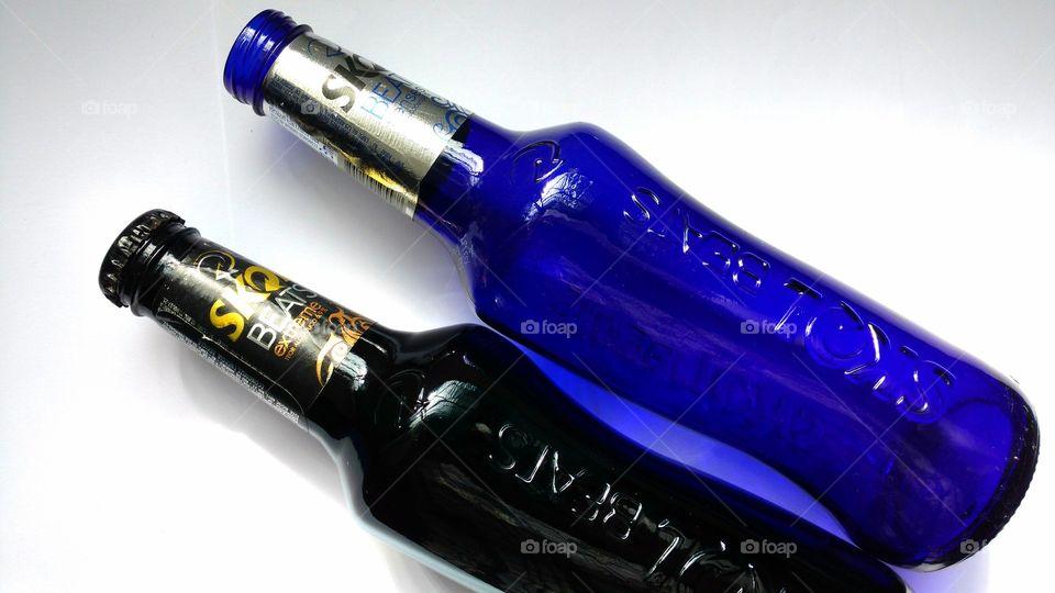 Garrafas coloridas long necks, com design elegante, de cerveja Skol Beats.