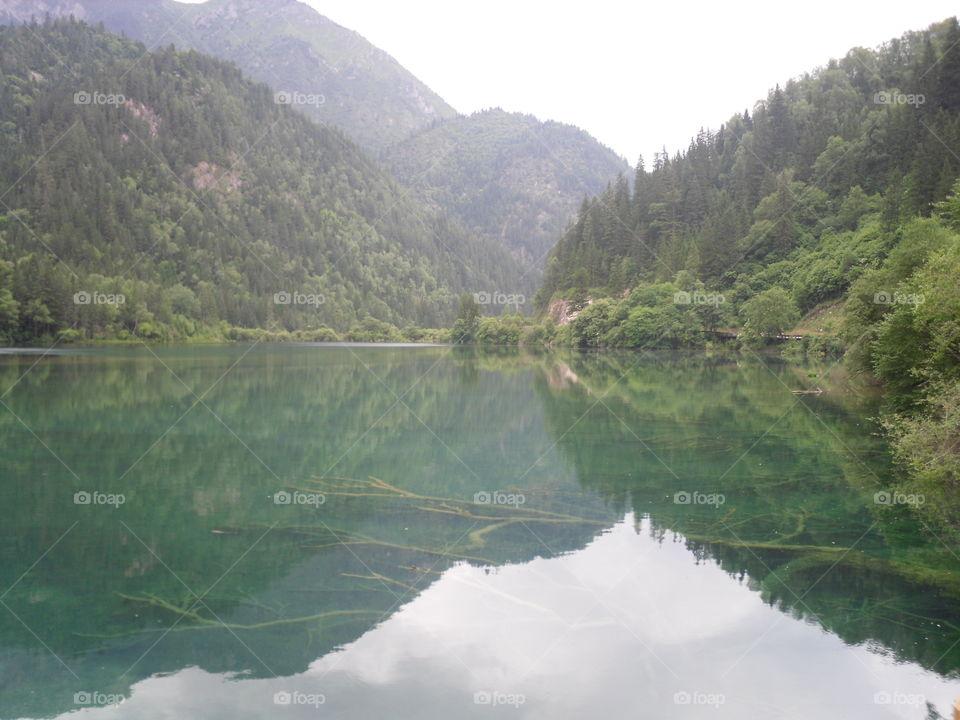 Green mountain reflecting on lake