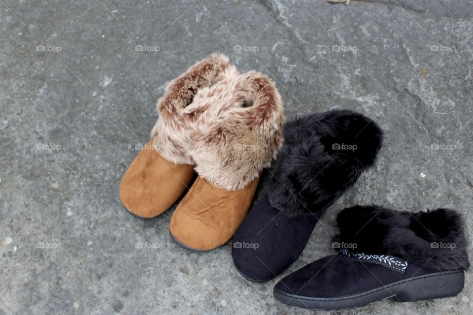 Tan and Black Faux Fur Slippers on rock