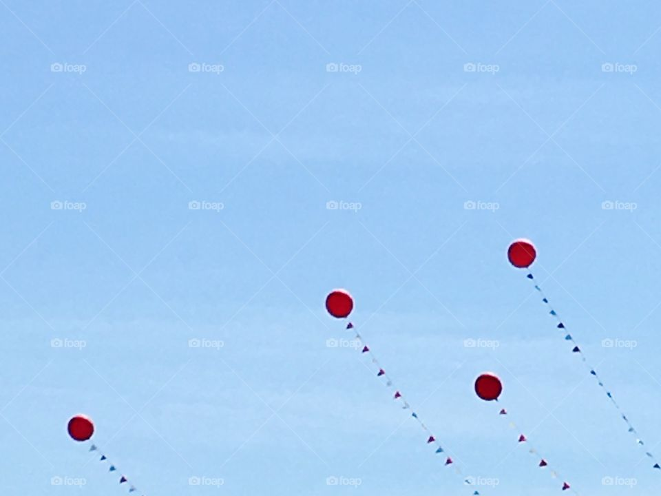 Red balloons floating in the blue sky.