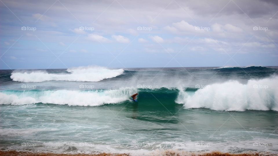 Surfing on the big wave at Sandy beach in Hawaii