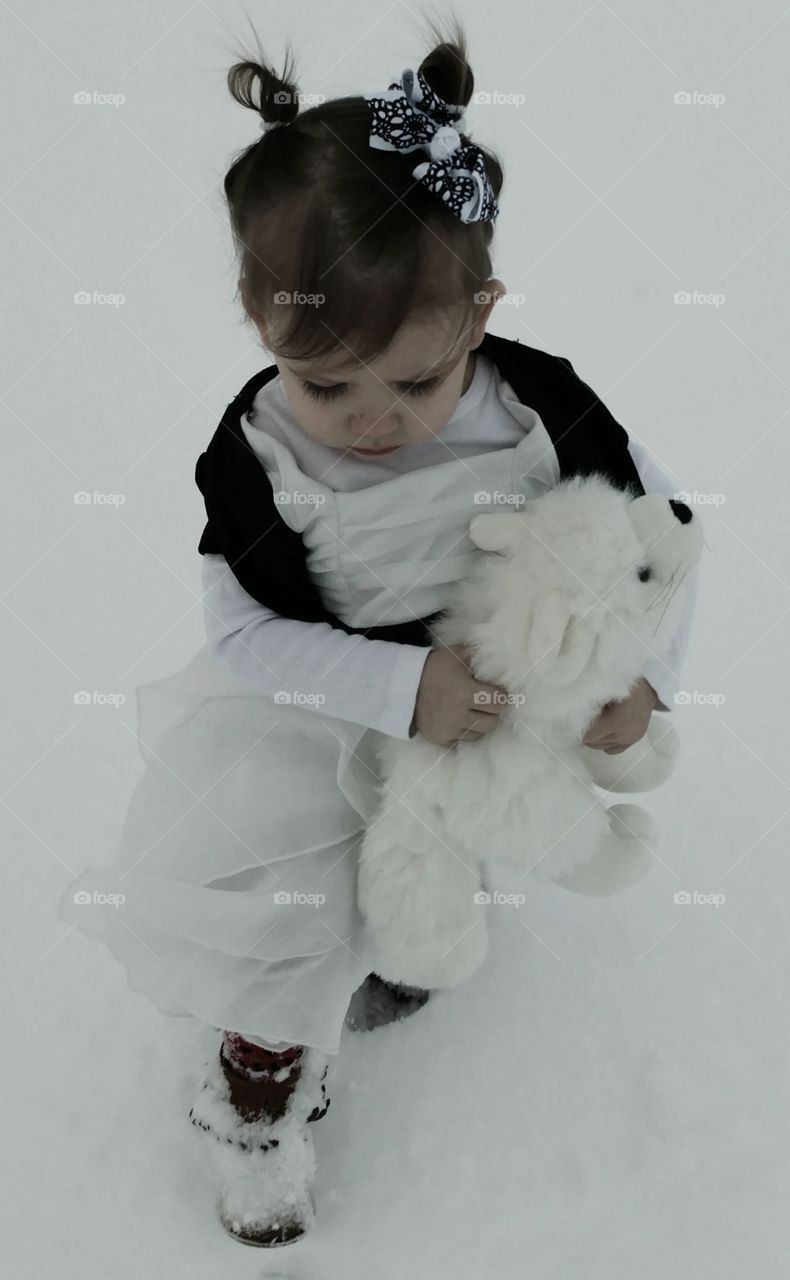 Cute girl standing with toy in winter