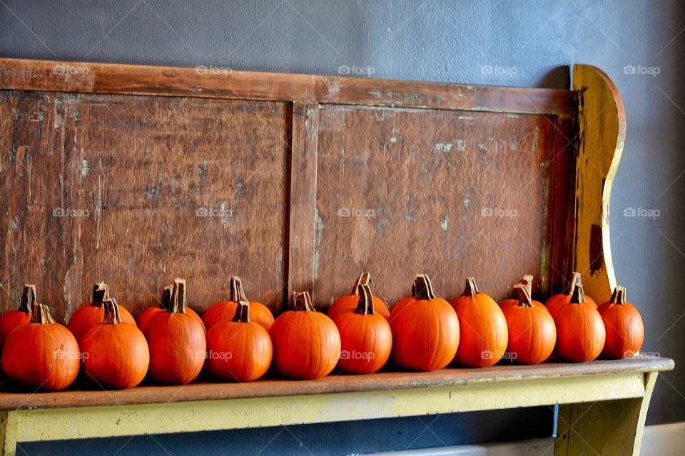 Pumpkins for sale arranged on a old church pew