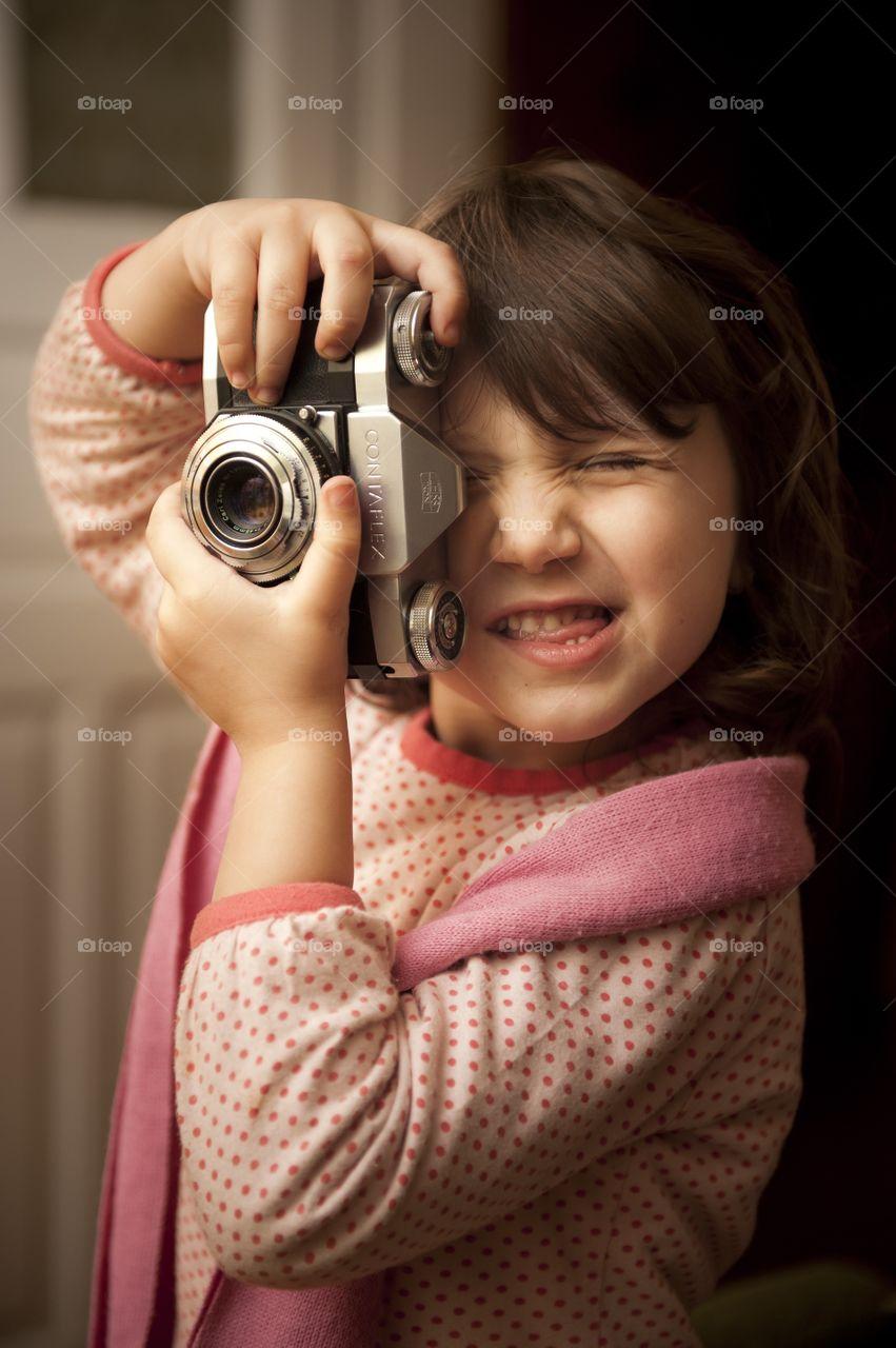 Cute girl taking photograph