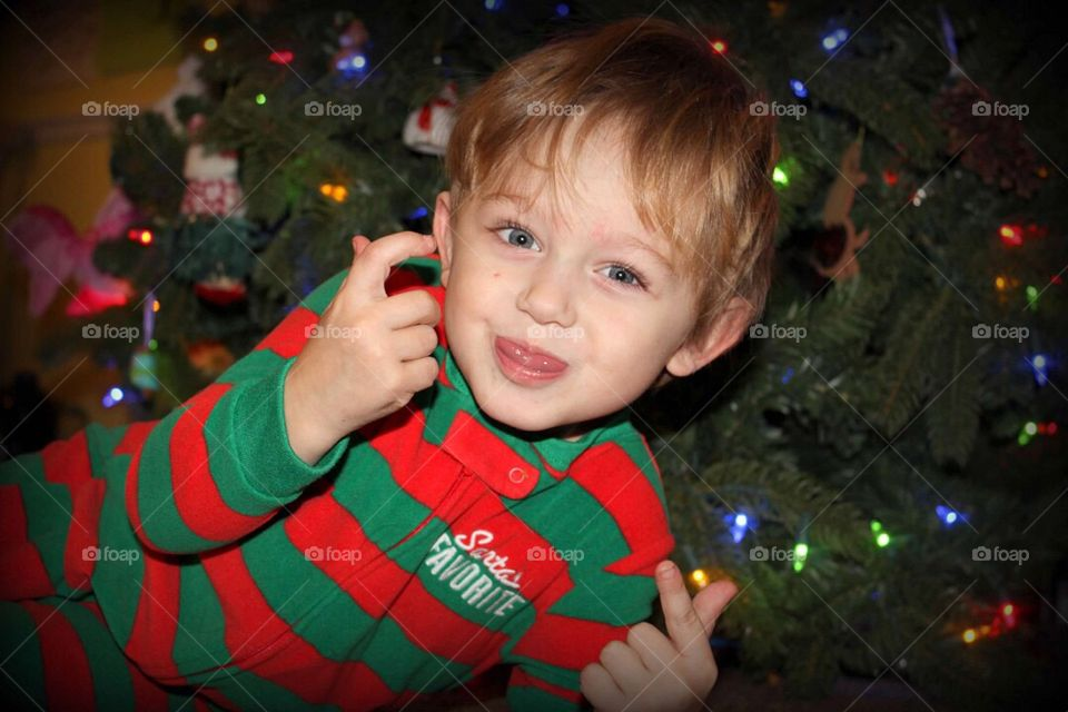 Boy sitting in front of illuminated christmas tree